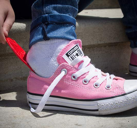 A kid uses a Little Piggie Shoehorn to get on her shoes.