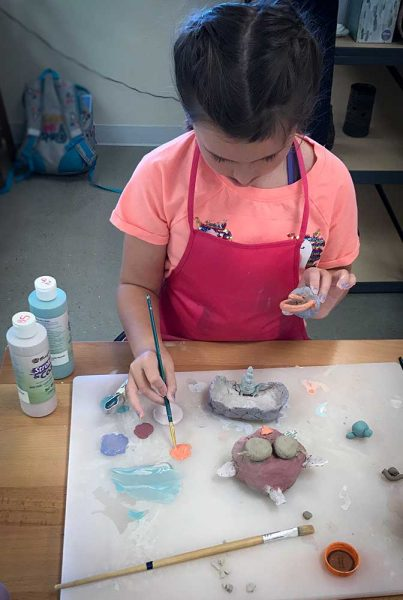 An ABQ Kid carefully glazes a creature she made out of clay at Creativity Warehouse's Saturday Kids Project.